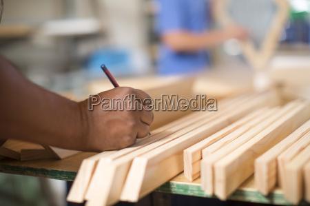 man in canvas workshop marking piece