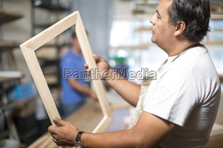 man looking at wooden frame for