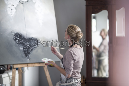 female painter painting on canvas