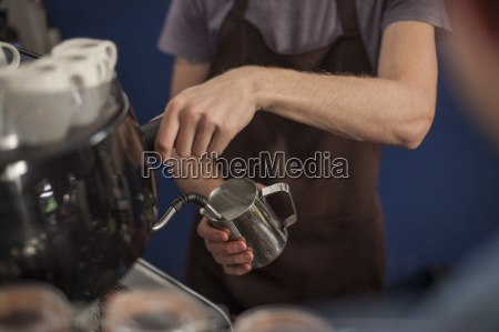young barista frothing milk from jug