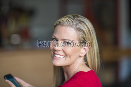 portrait of smiling woman holding cell