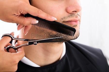 hairdresser shaping mans beard with scissor