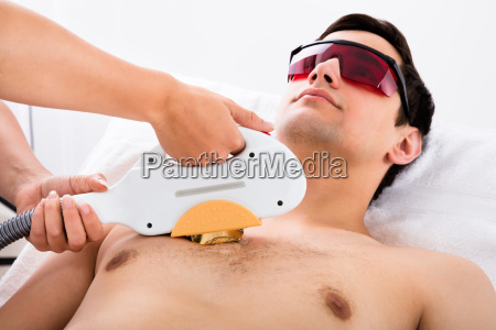 therapist giving laser epilation treatment to