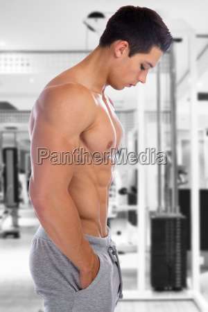 muscular young man looks down bodybuilder