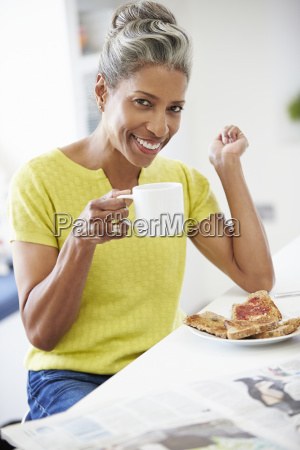 mature woman eating breakfast and reading