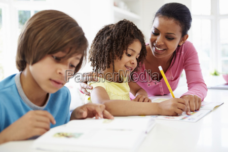 mother helping children with homework in