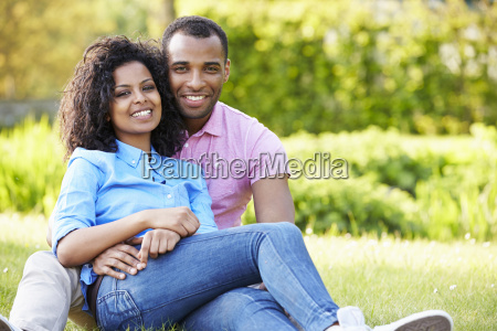 romantic young couple sitting in garden