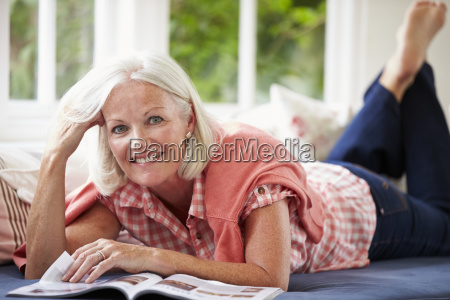middle aged woman reading magazine lying
