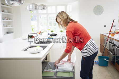 woman, standing, in, kitchen, emptying, waste - 19365742
