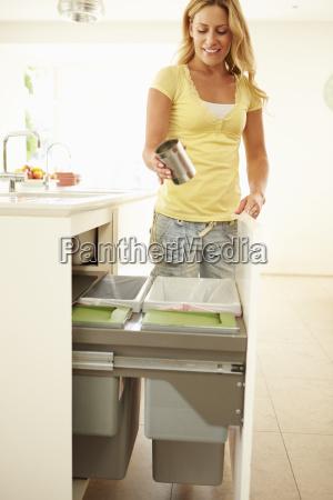 woman recycling kitchen waste in bin