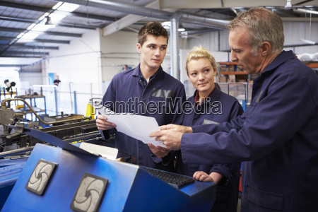 engineer teaching apprentices to use tube