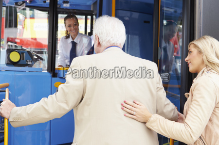 woman helping senior man to board