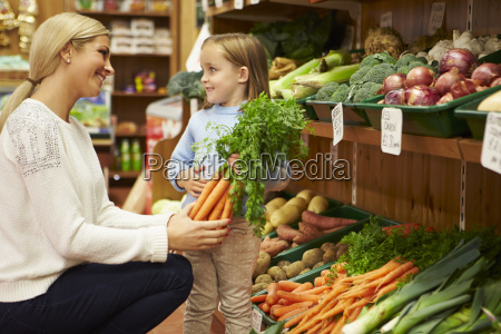 mother and daughter choosing fresh vegetables