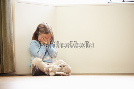 unhappy child sitting on floor in