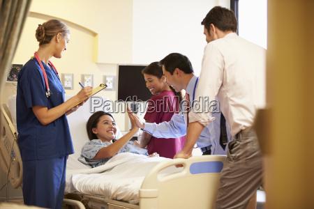 medical team meeting around female patient