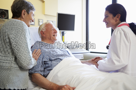 female doctor talking to senior couple