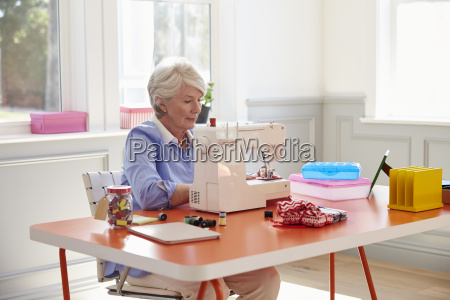 senior woman making clothes using sewing