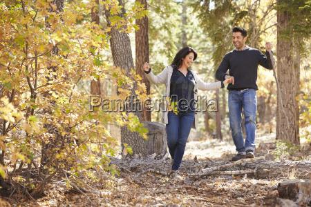happy hispanic couple hold hands hiking
