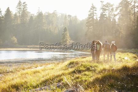 five friends walking near a lake