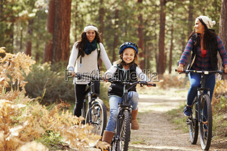 lesbian couple cycling in a forest