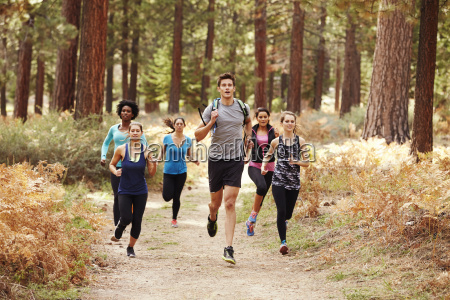 group of young adult friends running