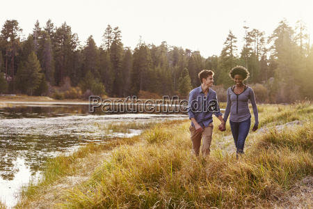 mixed race couple holding hands walking