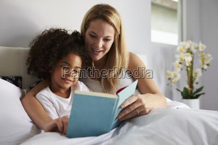 caucasian mum and black daughter read