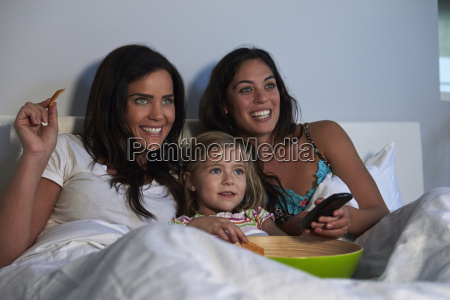 young girl watching tv in bed