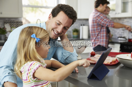 girl uses tablet in kitchen with