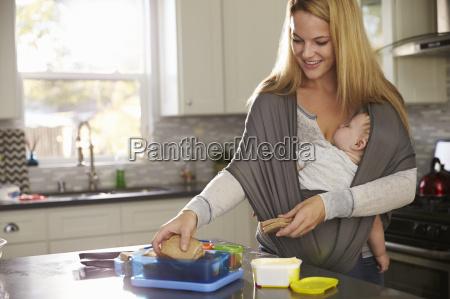 mum preparing lunchbox while baby sleeps