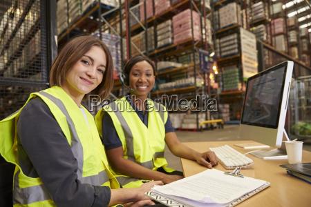 zwei weibliche kollegen in einem lagerbuero