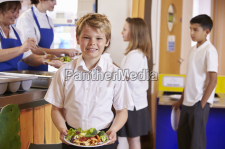 blonde haired boy holding plate of