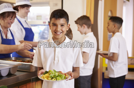 hispanic schoolboy holds a plate of