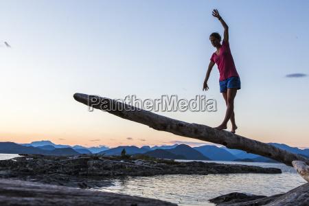 a young woman balances on a