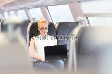woman travelling by train working on