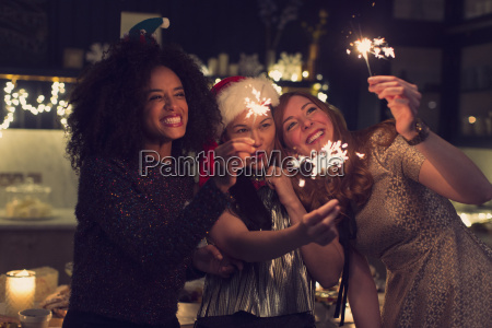 playful young women with sparklers