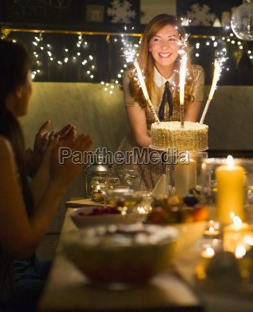 enthusiastic woman serving cake with sparkler