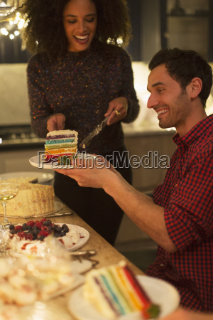 woman serving layer cake to man