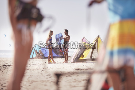 people with kiteboarding equipment talking on