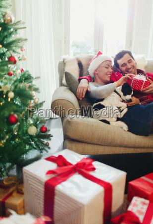 couple, cuddling, on, sofa, with, dog - 19399216