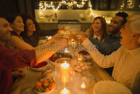 friends, toasting, champagne, glasses, at, candlelight - 19399220