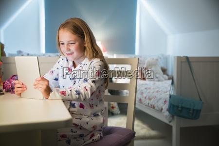 girl in pajamas using digital tablet
