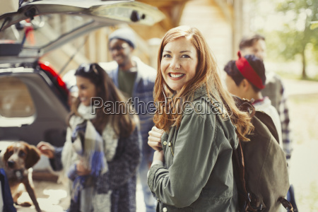portrait smiling hiker holding backpack with