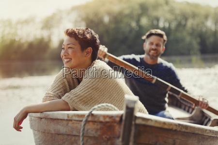 smiling couple canoeing on sunny lake