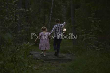 brother and sister walking with lantern