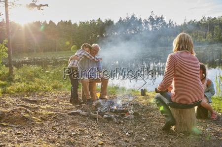 grandparents and grandchildren hugging at campfire