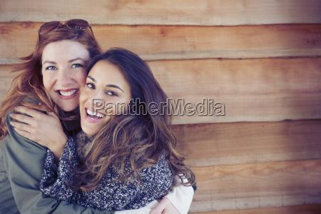 portrait enthusiastic smiling female friends hugging
