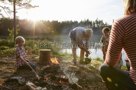 grandparents and grandchildren at campfire at