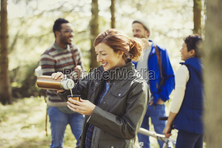 smiling woman hiking pouring coffee from