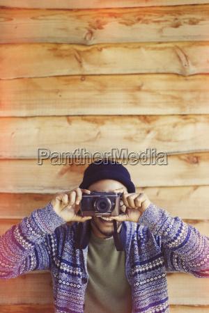 portrait playful man using camera outside